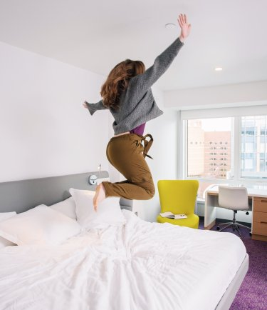 YOTEL Boston - guest jumping in the bed